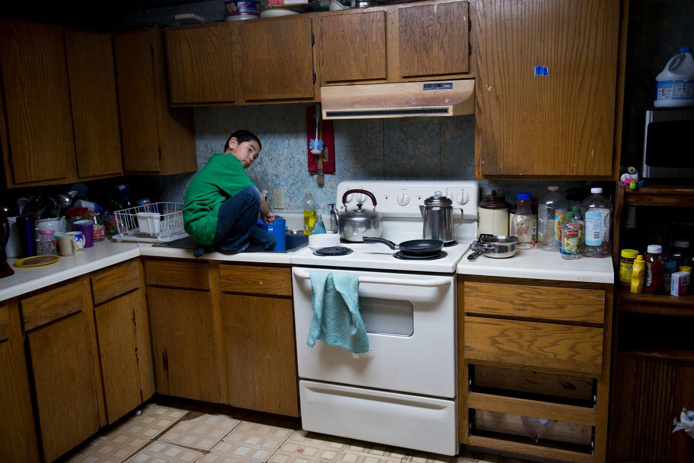 Lucas Penayah, 7, makes juice in Harriet Penayah's home in Savoonga. (Marc Lester / Alaska Dispatch News)