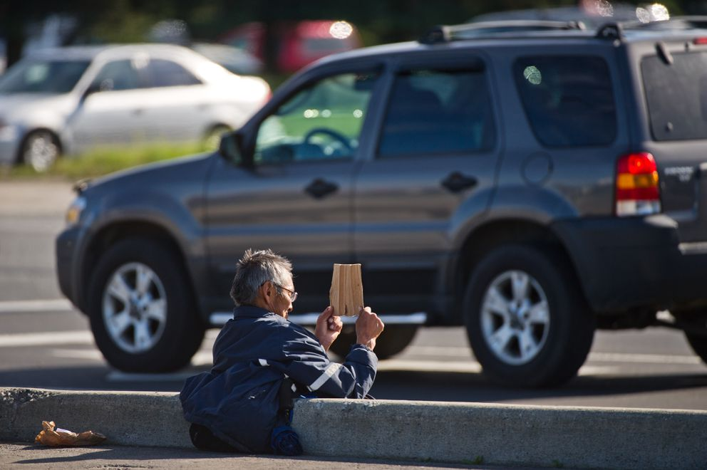A man holds a sign to passing motorists on Friday, September 9, 2016. Anchorage. The Anchorage Economic Development Corp. is launching a public awareness campaign to deter panhandling. (Marc Lester / Alaska Dispatch News)