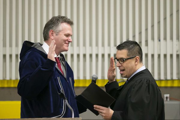 Mike Dunleavy, left, is sworn into office as Alaska's governor by Superior Court Judge Paul Roetman in Kotzebue, Alaska, on Monday, Dec. 3, 2018. Poor visibility forced Dunleavey's swearing-in ceremony to be held in Kotzebue instead of Noorvik, Alaska, his wife's hometown. (Stanley Wright/Alaska Governor's Office via AP)