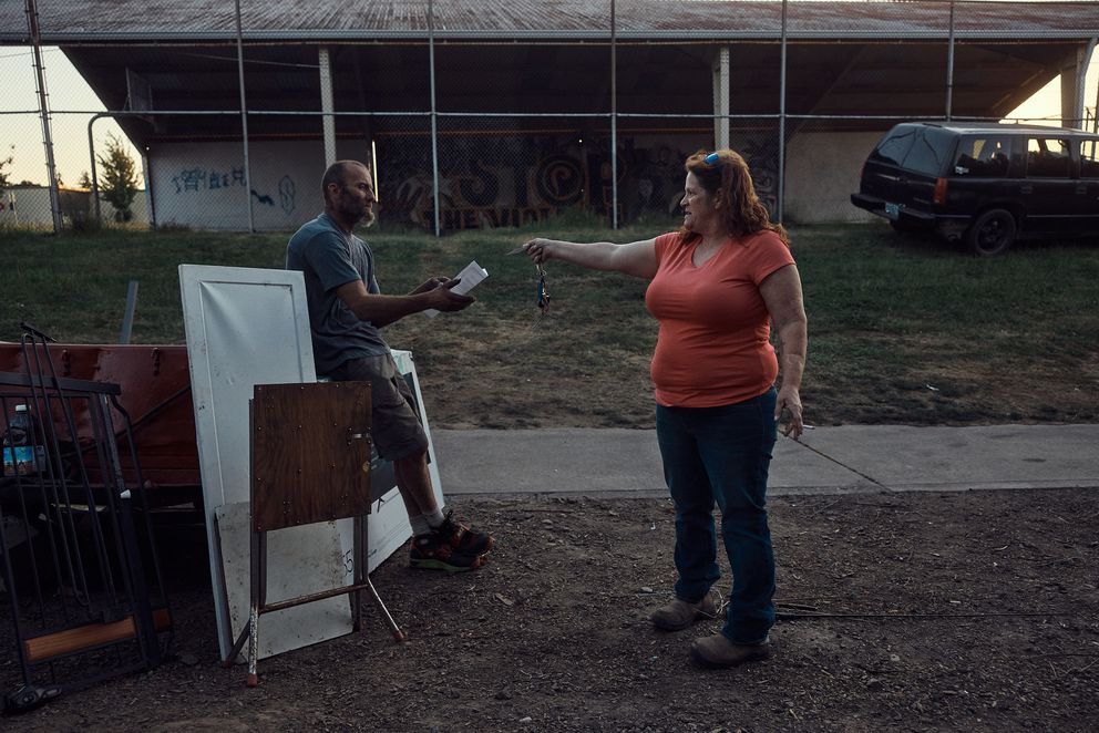 Shannon Stickler hands Jeremy the keys to her newly acquired storage unit. She had met him six months earlier, after she discovered that her daughter was stopping by the homeless encampment, top, after school and had befriended a few residents. Photo by Mason Trinca for The Washington Post