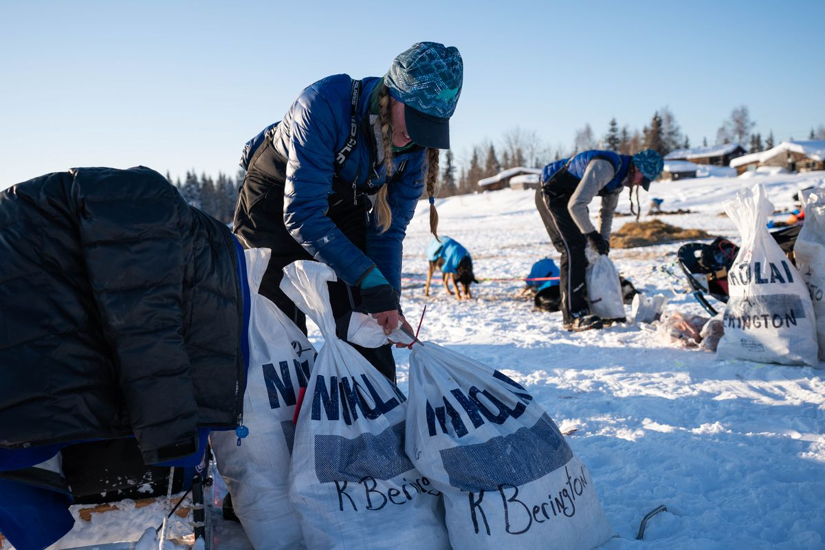 Kristy and Anna Berington open bags of food after arriving in Nikolai on Tuesday. (Loren Holmes / ADN)
