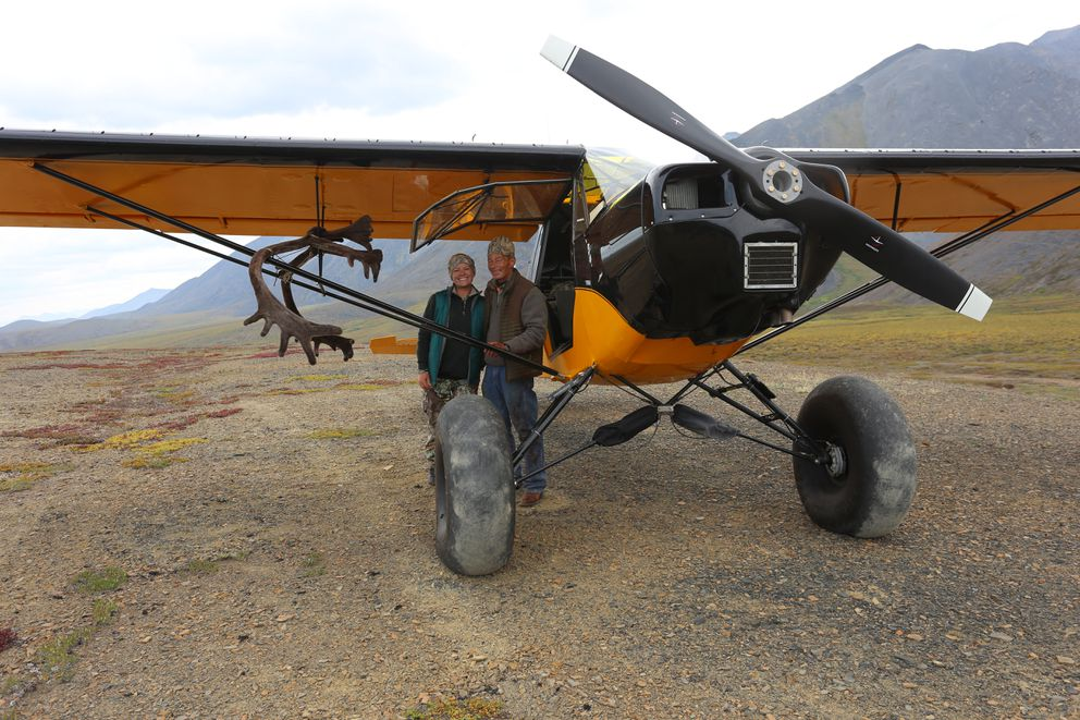 Christine Cunningham and Steve Meyer stand beside a modified PA-12 Super Cub owned by Matt Thoft of Silvertip Aviation during a Brooks Range caribou hunt in 2015.  (Photo by Matt Thoft)
