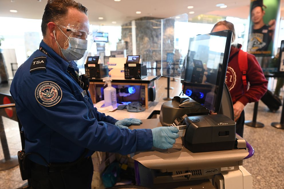 Transportation Security Officer Fred Kring, scans a travelers photo identification with a new Credential Authentication Technology (CAT) to verify the authenticity of the credential and confirm flight status at the TSA security screening in the Ted Stevens Anchorage International Airport. (Bill Roth / ADN)