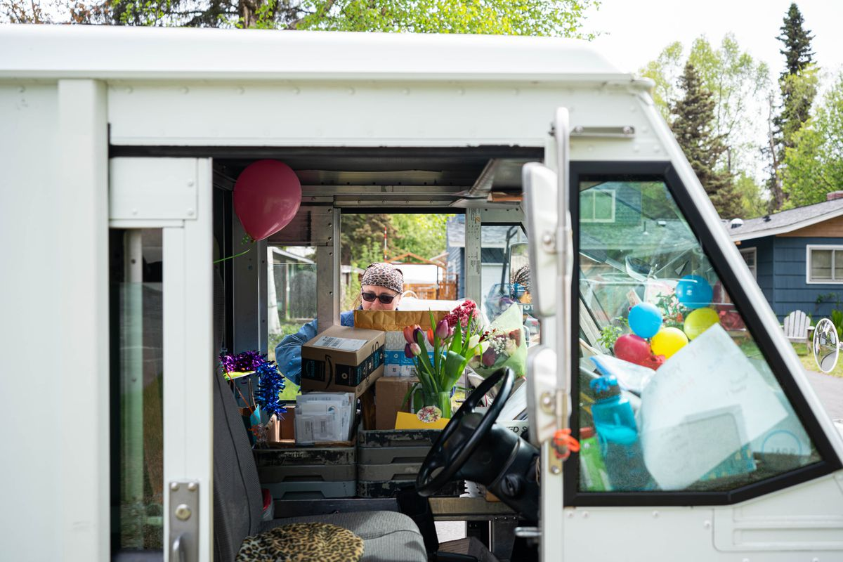 Mail carrier Weeze Smoke's truck is filled with flowers and homemade signs on Saturday, May 23, 2020 in Turnagain. Smoke has delivered the mail in this neighborhood for the past 15 years and Saturday was her last day on the job before retiring. (Loren Holmes / ADN)