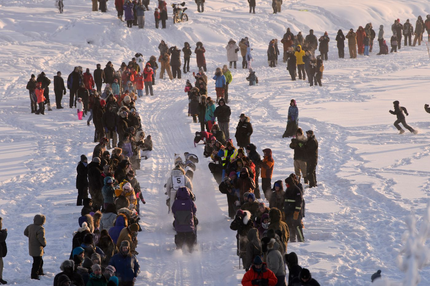 Denis Tremblay mushes by fans on the Chena River in Fairbanks. (Marc Lester / Anchorage Daily News)