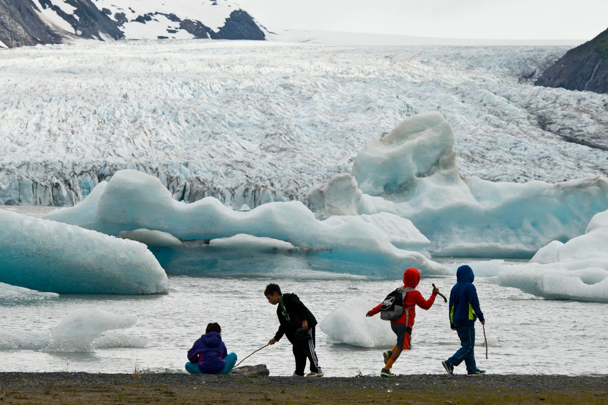 Kids explore the waterline at Spencer Lake with a good view of Spencer Glacier and some of its icebergs on Saturday, June 11, 2016. Hikers can access the area, south of Portage in Chugach National Forest, by way of Alaska Railroad's whistle stop service, which drops passengers about a 1.3-mile walk from the lake. (Marc Lester / Alaska Dispatch News)