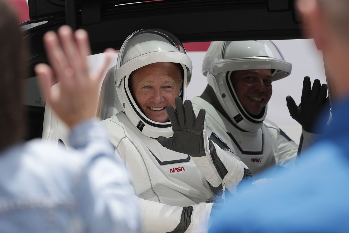 NASA astronauts Douglas Hurley, left, and Robert Behnken ride a Tesla SUV from the Neil A. Armstrong Operations and Checkout Building on their way to Pad 39-A, at the Kennedy Space Center in Cape Canaveral, Fla., Wednesday, May 27, 2020. The two astronauts will fly on a SpaceX test flight to the International Space Station. For the first time in nearly a decade, astronauts will blast into orbit aboard an American rocket from American soil, a first for a private company. (AP Photo/John Raoux)