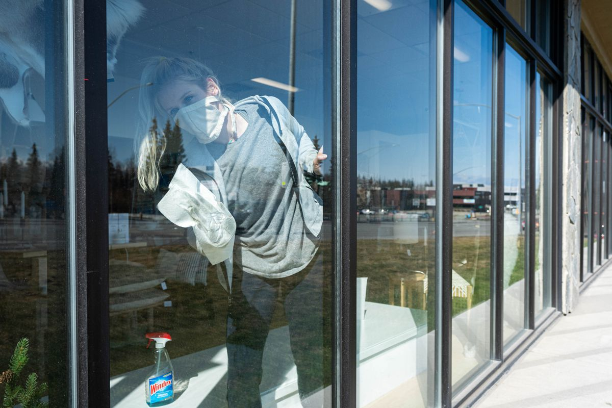 The Nordic Home owner Erika Klaar cleans windows on Saturday, April 25, 2020. Klaar says she is hoping to open her furniture and home goods store on Tuesday. (Loren Holmes / ADN)