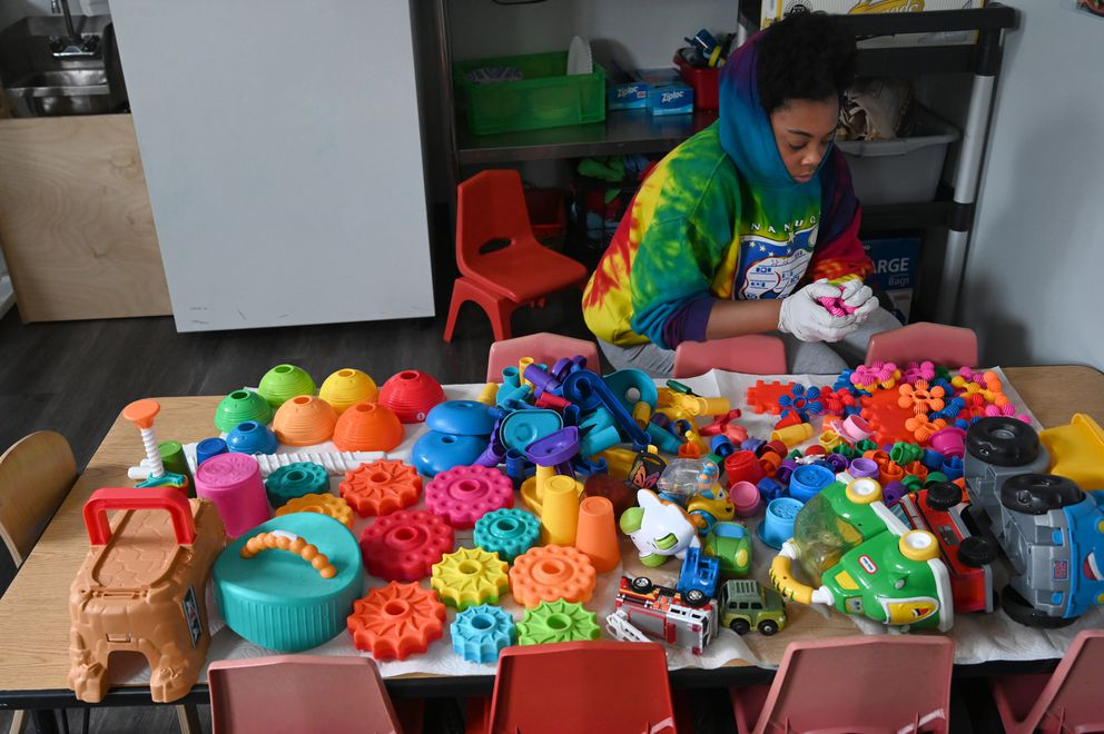 Lex Tejada cleans toys during nap time at Hillcrest Children's Center, Monday, March 17, 2020. (Anne Raup / ADN)