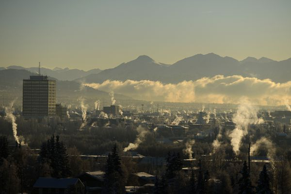 A low cloudbank stretches into Turnagain Arm as steam rises from buildings on a cold morning in Anchorage, Alaska on Wednesday, January 18, 2017. The Chugach and Kenai Mountains form a backdrop for the chilly scene. (Bob Hallinen / Alaska Dispatch News)