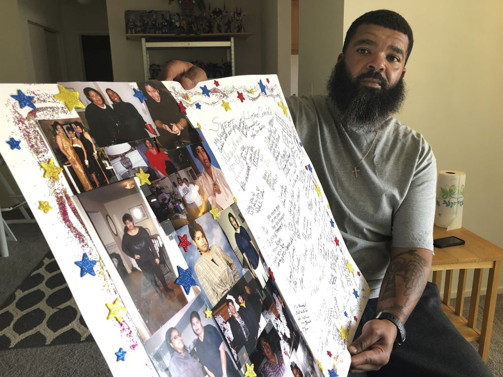Roland Mack holds a poster with pictures and messages made by family members in memory of his sister, Chantee Mack, in District Heights, Md., on Friday, June 19, 2020. (AP Photo/Federica Narancio)