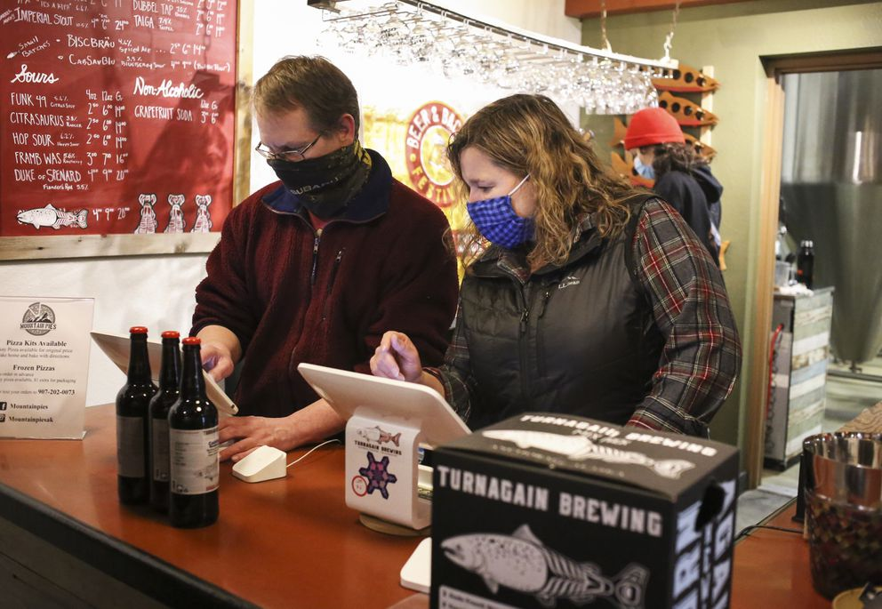 Ted and Mary Rosenzweig, owners of Turnagain Brewing in Anchorage, sell to-go beers to a customer on Thursday, Dec. 3, 2020. (Emily Mesner / ADN)