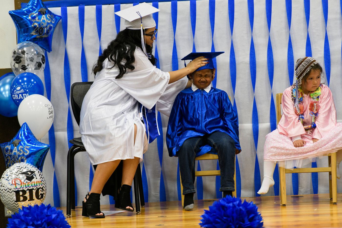 Denise Kalmakoff shares the stage with the school's incoming kindergartners, Joseph Amodo White and Serenity Simeonoff, on May 16. (Marc Lester / ADN)