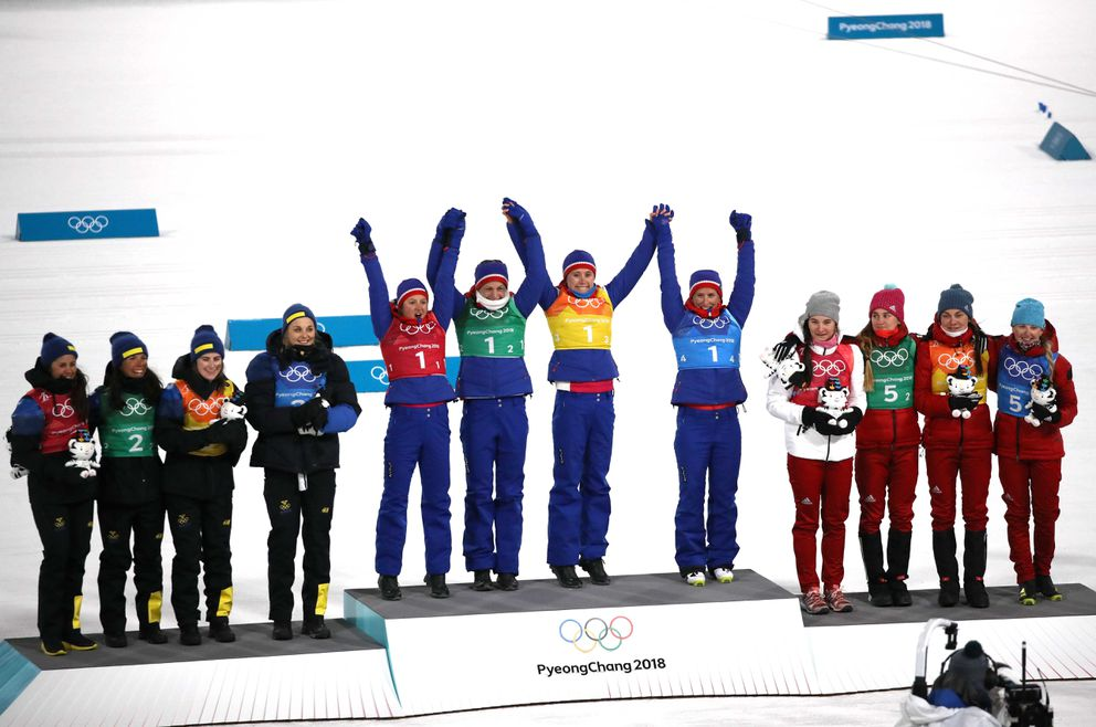 Women's 4×5 cross-country relay: Gold medalists Ingvild Flugstad Oestberg, Astrid Uhrenholdt Jacobsen, Ragnhild Haga and Marit Bjoergen of Norway, Silver medalists Anna Haag, Charlotte Kalla, Ebba Andersson and Stina Nilsson of Sweden and Bronze medalists Olympic athletes from Russia, Natalia Nepryaeva, Yulia Belorukova, Anastasia Sedova and Anna Nechaevskaya celebrate during the victory ceremony. REUTERS/Carlos Barria