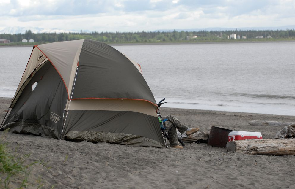 A man's legs poke out of the front of a tent on the north Kenai beach on Sunday, June 16, 2019. (Matt Tunseth / ADN)