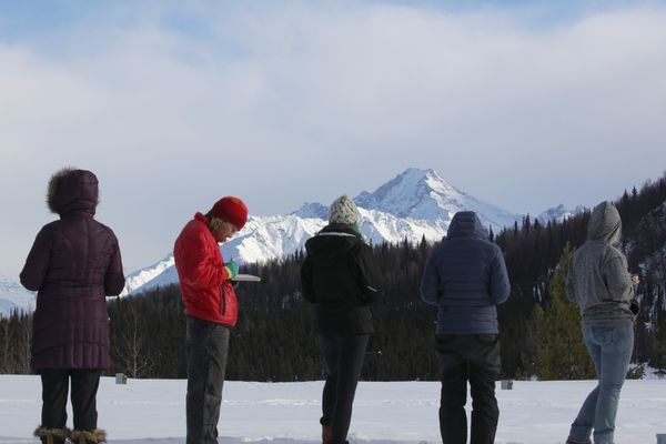 A group of women write haiku at the 2018 Becoming an Outdoors Woman Winter Workshop. The Talkeetna Mountains are in the background. (Photo by Steve Meyer)