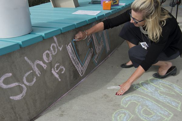 """Anchorage School District Superintendent Deena Bishop borrows a phrase popular with young people as she writes """"School is lit"""" in chalk in front of Airport Heights Elementary. (Marc Lester / ADN)"""