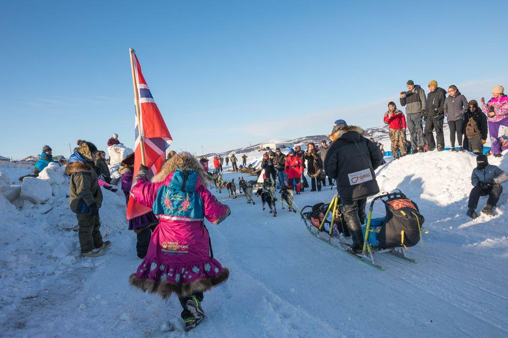 Carrying a Norwegian flag, DeeDee Jonrowe runs after neighbor Joar Liefseth Ulsom as he arrives in Unalakleet. (Loren Holmes / ADN)