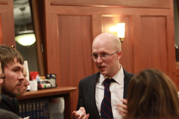 Sitka Democratic Rep. Jonathan Kreiss-Tomkins speaks with legislative aides during a break from House floor debate at the Capitol on Thursday, March 16, 2017.