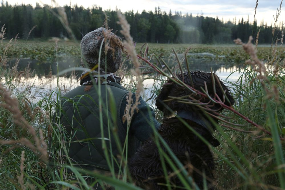 Christine Cunningham and Cheyenne sit at the edge of a pond waiting for ducks together. (Photo by Steve Meyer)