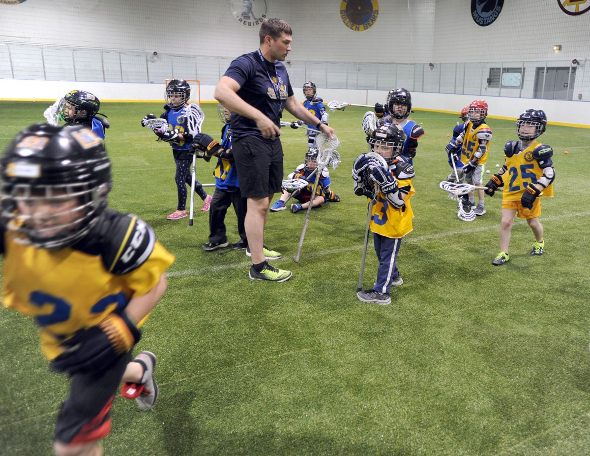Coach Kirk Kullberg circles up with the 8U group of lacrosse players.  (Anne Raup / ADN)