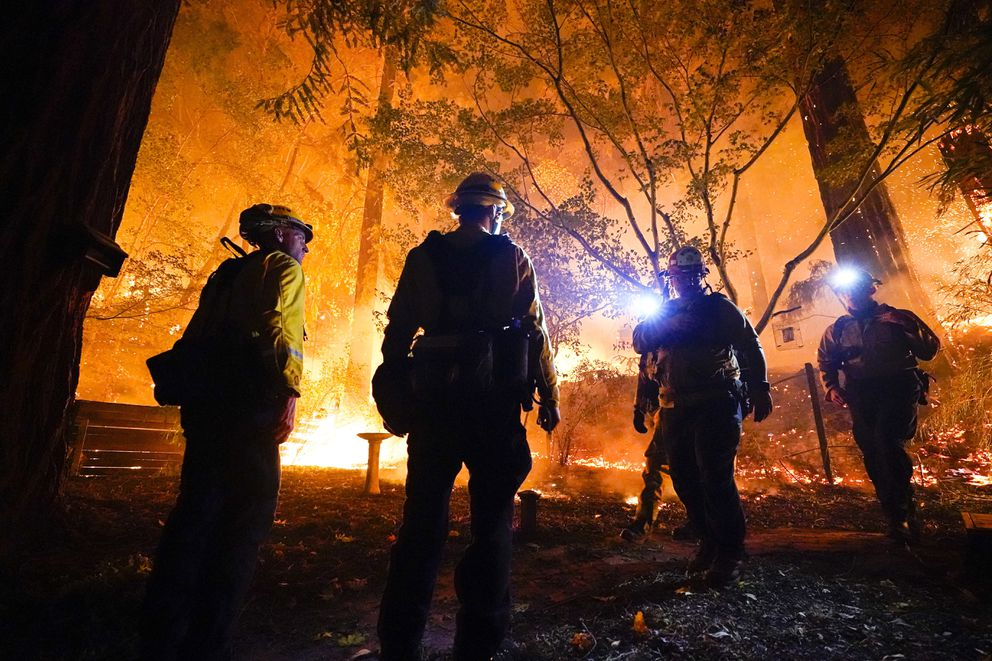 FILE - In this Aug. 21, 2020, file photo, firefighters make a stand in the backyard of a home in front of the advancing CZU August Lightning Complex Fire in Boulder Creek, Calif. Two unusual weather phenomena combined to create some of the most destructive wildfires the West Coast states have seen in modern times. (AP Photo/Marcio Jose Sanchez, File)