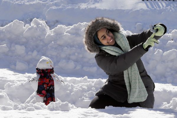 DePaul University student Alaa Hejazi, from Riyadh, Saudi Arabia, shoots a selfie with her very first snowman Monday, Feb. 2, 2015, in Chicago's Millennium Park. The National Weather Service said that the 19.3 inches of snow in Chicago was the fifth highest snowfall total since records started being kept in the late 1800s.