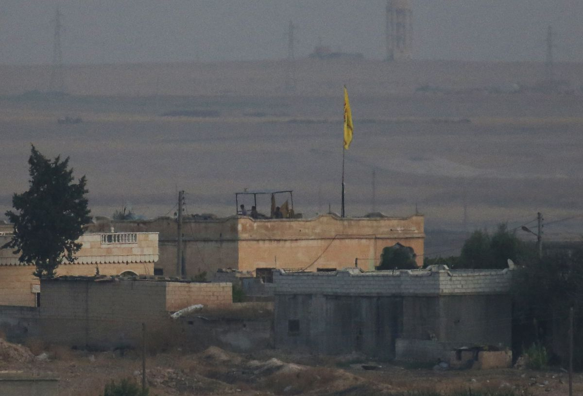 In this photo taken from the Turkish side of the border between Turkey and Syria, in Akcakale, Sanliurfa province, southeastern Turkey, members of the Kurdish People's Protection Units, or YPG, hold a position on a building in the Syrian town of Tel Abyad, Tuesday, Oct. 8, 2019. The Turkey - Syria border has became a hot spot as Turkish Vice President Fuat Oktay said Turkey was intent on combatting the threat of Syrian Kurdish fighters across its border in Syria. (AP Photo/Lefteris Pitarakis)