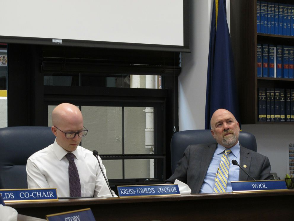 Alaska state Rep. Adam Wool, D-Fairbanks, right, listens to testimony given by phone on the nomination of Amanda Price to be state public safety commissioner on Thursday, April 11, 2019, in Juneau. Also shown is Rep. Jonathan Kreiss-Tomkins, D-Sitka. (AP Photo/Becky Bohrer)
