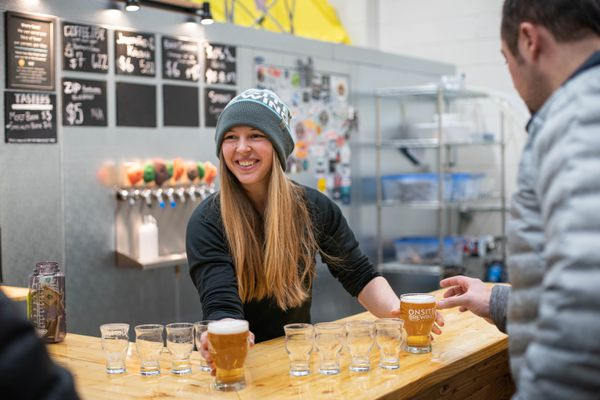 Onsite Brewing co-owner Amber Jackson serves beer on Thursday, Dec. 5, 2019 during the brewery's soft opening. (Loren Holmes / ADN)