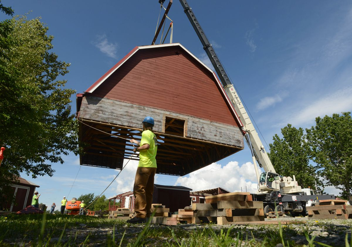 A crane lifts the roof off of the Colony barn visitors center at the Musk Ox Farm as Xavier Lechleitner helps guide it to its resting place on Thursday. (Photo by Bob Hallinen)