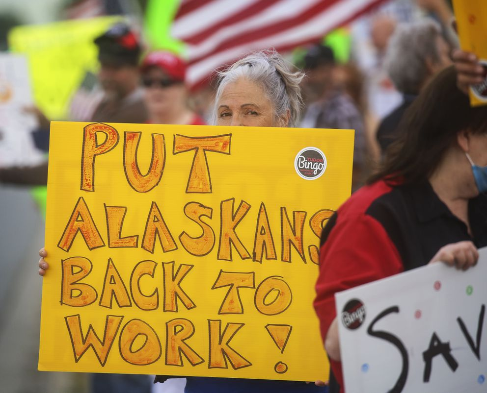 A woman holds a sign while standing on the sidewalk along E. 36th Avenue to protest the newest public health mandate in Anchorage on Aug. 3, 2020. The emergency order limits gathering sizes, prohibit indoor dining at restaurants, require people to maintain small social bubbles and to work from home when possible. It will be in effect for the next four weeks. (Emily Mesner / ADN)