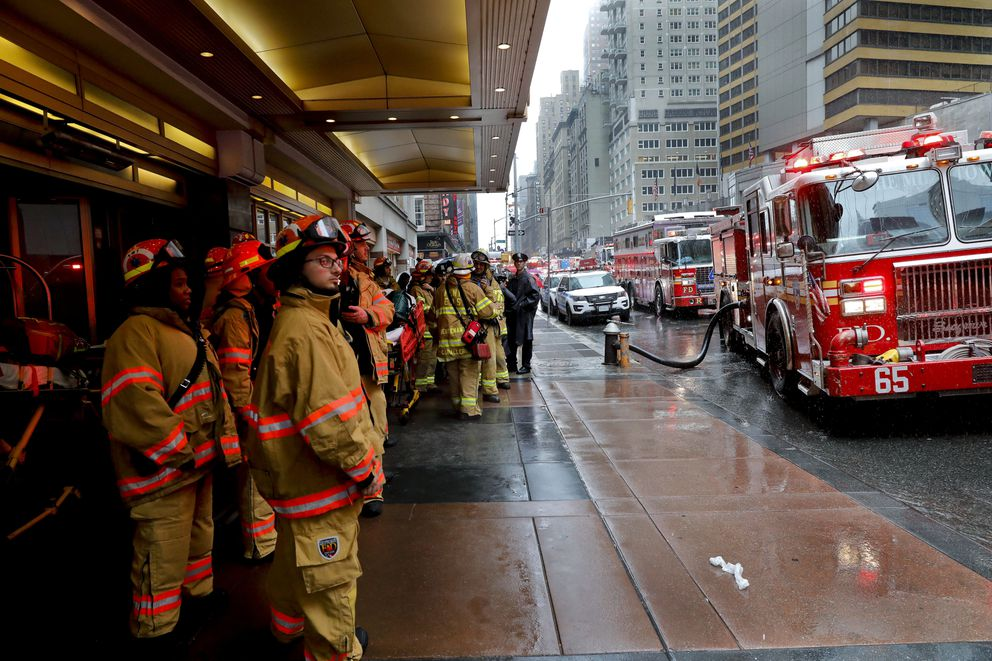 Firefighters respond to the scene where a helicopter crash-landed on the roof of a midtown Manhattan skyscraper, Monday, June 10, 2019, in New York. (AP Photo/Mark Lennihan)