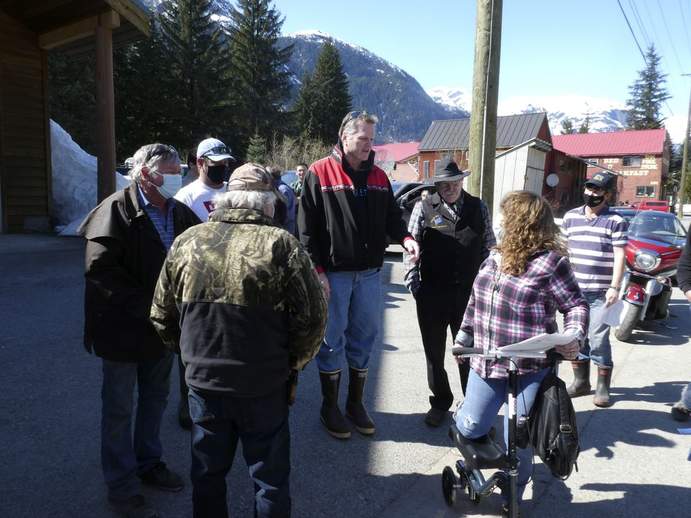 Alaska Gov. Mike Dunleavy, center, meets with people near an outdoor COVID-19 vaccination clinic in Hyder, Alaska, on Thursday, April 22, 2021. (AP Photo/Becky Bohrer)