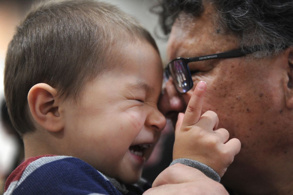 Konan Lind and his grandfather Orville Lind snuggle up during the Alaska Federation of Natives Convention at the Dena'ina Center in Anchorage, Alaska on Saturday, Oct. 21, 2017. The elder Lind was showing his artwork at the Alaska Native Customary Art Show. (Bob Hallinen / Alaska Dispatch News)