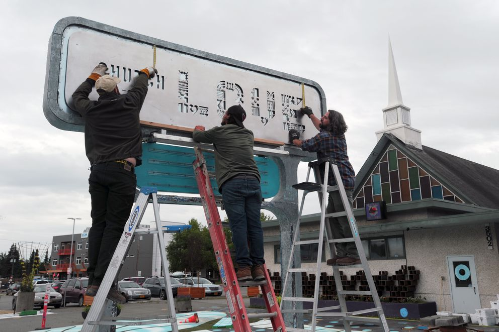 Zach Allen, Daniel Cox and Chad Taylor of Intrinsic Landscapes check the placement of a new sign for the Church of Love before removing it again for painting on Aug. 18 in Spenard. The sign, designed by Karen Larsen, was to be painted black and then lit from behind with LED light strips. (Erik Hill / Alaska Dispatch News)
